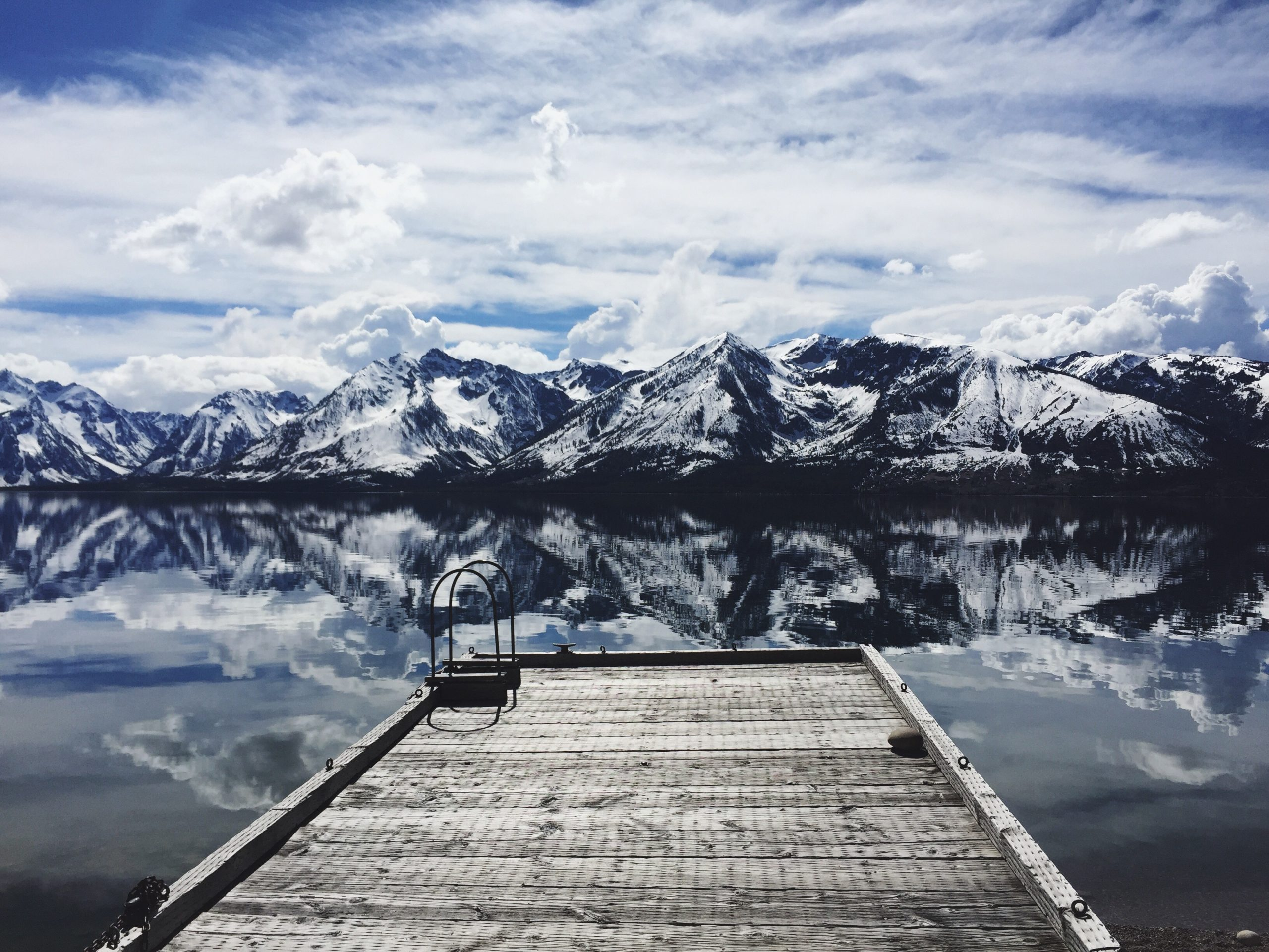 A wooden-plank dock on the edge of a clear lake with snowy mountains in the background