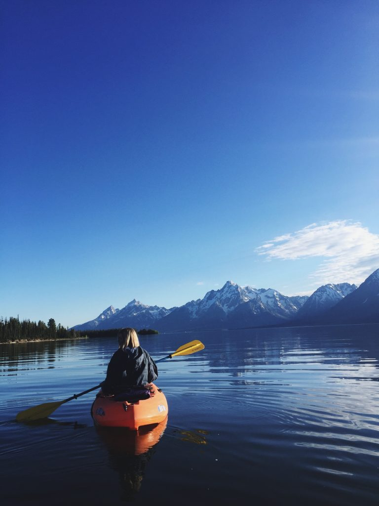 a woman kayaking on a large lake with mountains in the background on a clear day