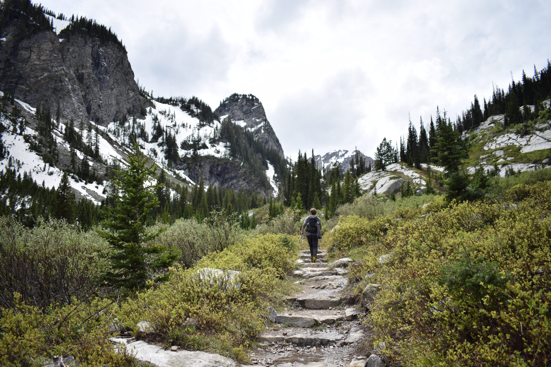 a man walking up steps on a hiking trail with mountains on either side